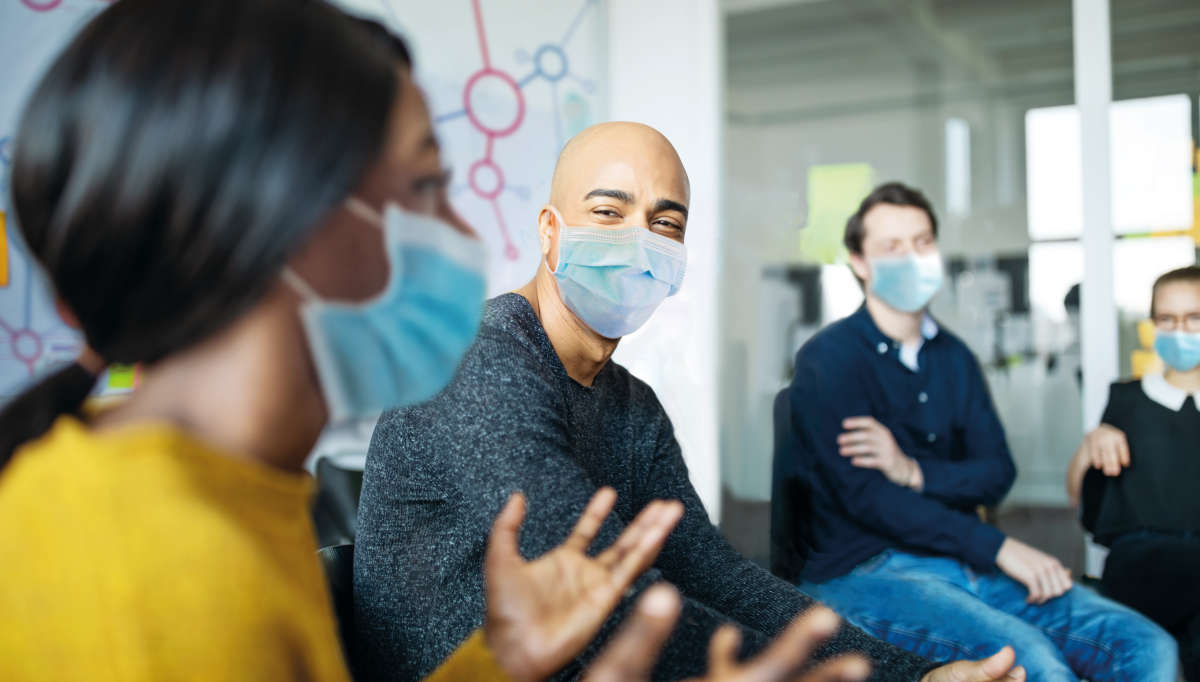 People wearing masks talking during a meeting