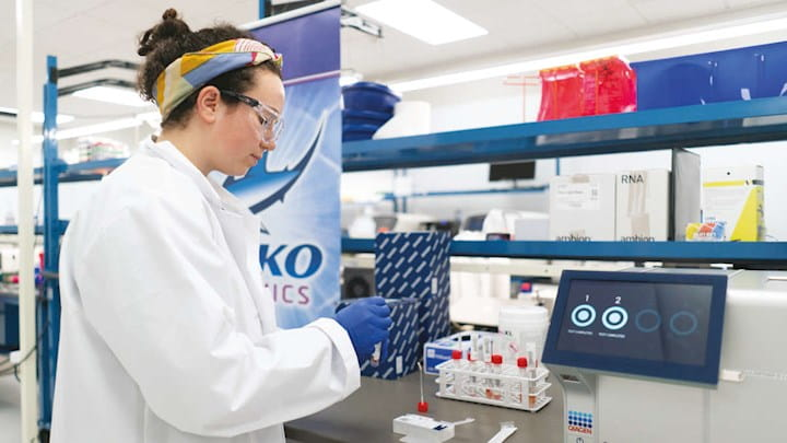 A woman wearing protective goggles and a lab coat in a lab