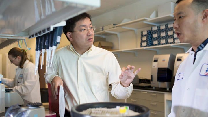 Bill Wang in a lab talking to a colleague