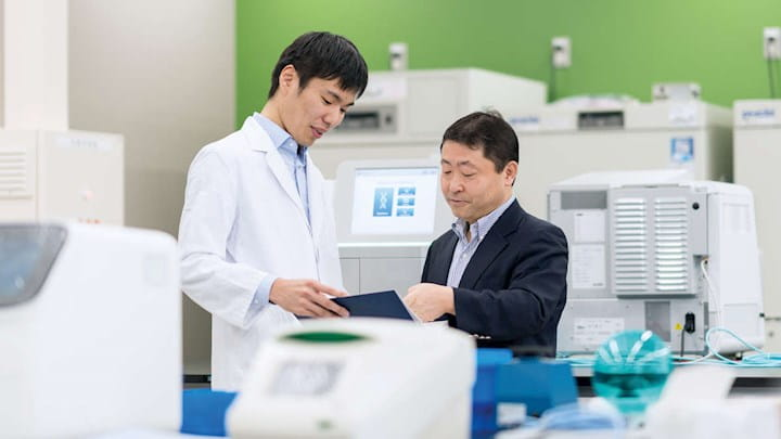 Two men discussing a document in a lab