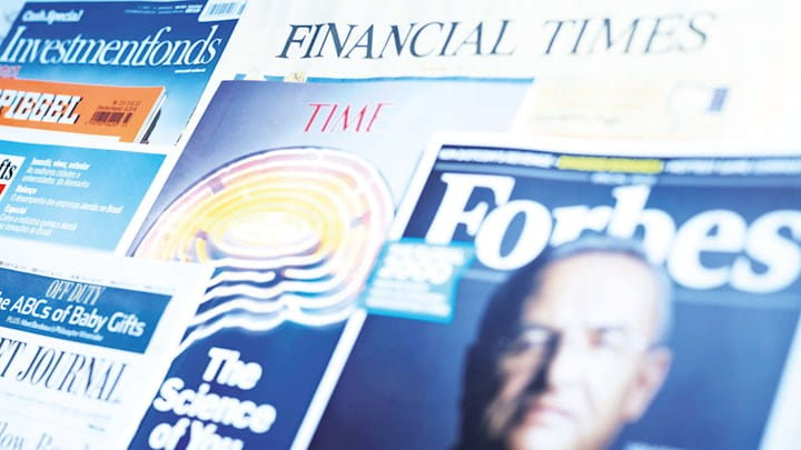 Close up of newspapers like Forbes, Financial Times and other