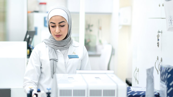 A woman wearing a head scarf and a lab coat in a lab