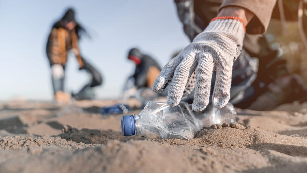 a person picking up an empty plastic bottle at a beach